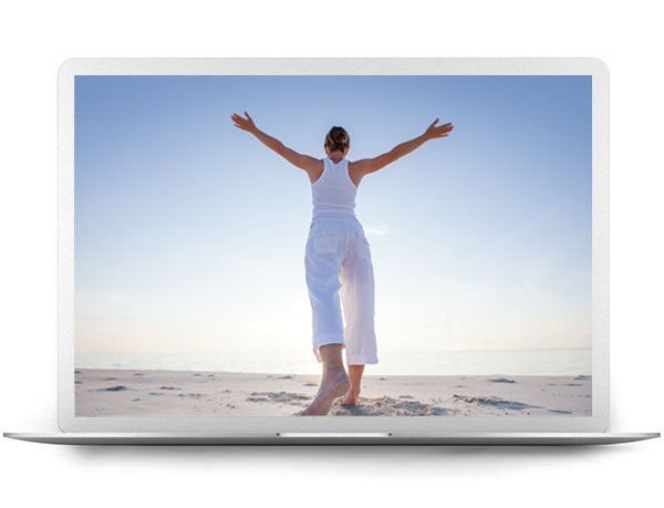 Laptop Screen Of Image Of A Woman Holding Arms Out Standing On A Beach