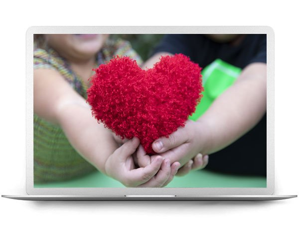 Laptop Displaying Kids Hands Holding A Fluffy Heart Toy
