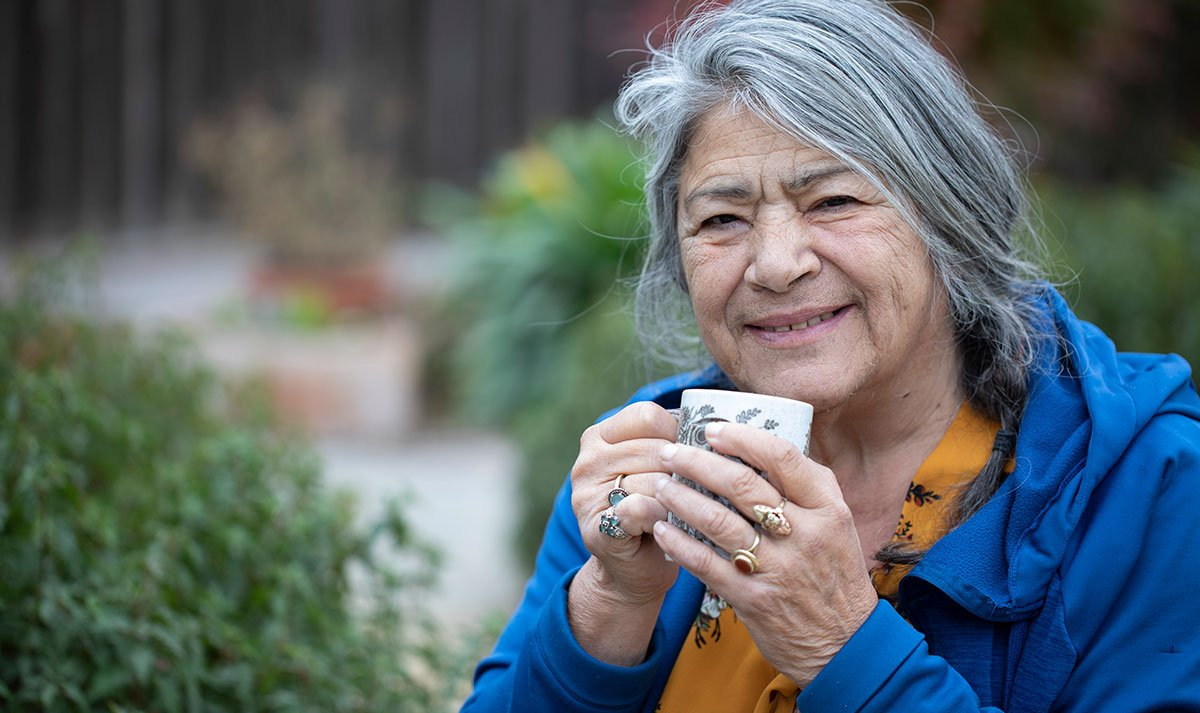 Gray Haired Woman Holding A Cup In The Outdoors